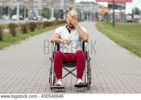 A Man Sits In A Wheelchair, Faced With Difficulties Alone, Depression. The Concept Of A Wheelchair,