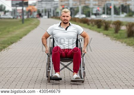 A Disabled Man Sits In A Wheelchair On The Street. The Concept Of A Wheelchair, Disabled Person, Ful