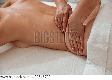 Masseuse Hands Massaging Female Body In Spa Salon