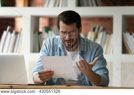Young Man Holding Paper Letter Reading Shocking Unpleasant Unexpected News