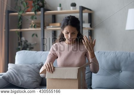 Woman Unpacking Box Feels Dissatisfied By Received Post Parcel