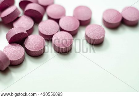 Purple Pills Scattered On A White Background, Food Supplements Which Includes Acai Berries