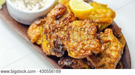 Delicious Onion Bhaji Fritters Served On Wooden Plate With White Dip