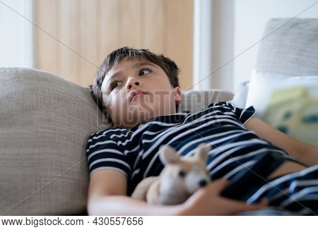 Happy Boy Lying On Sofa Looking Up Watching Cartoon On Tv. Mixed Race Child Resting In Living Room W