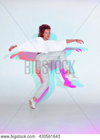 Dancing Young Mixed Race Girl In Colourful Light. Female Dancer Performer Showing Hip Hop Dance