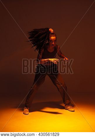 Dancing Mixed Race Girl Inshadow In Studio. Female Dancer Performer Moving In Expressive Ethnic Hip