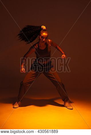 Dancing Athletic Mixed Race Girl Performing Expressive Fiery Hip Hop Or Ethnic African Modern Dance