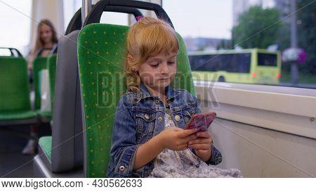 Joyful Child Girl Citizen Playing On Smartphone, Chatting, Texting, Browsing Social Media While Trav