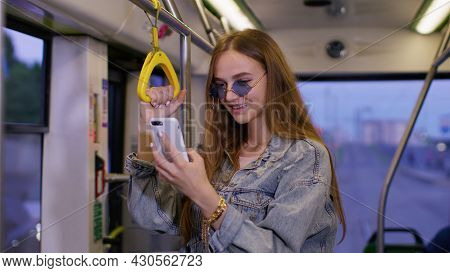 Young Woman Playing On Smartphone, Chatting, Texting, Browsing Social Media While Traveling By Bus T