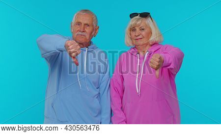 Upset Senior Old Retired Grandfather Grandmother Showing Thumbs Down Sign Gesture, Expressing Discon
