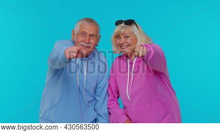 Amused Senior Couple Man Woman Grandparents Pointing Finger To Camera, Laughing Out Loud, Taunting M