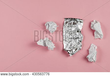 Crumpled Foil And Scraps Of Paper Against A Pink Background. Piece Of Aluminum Foil For Food Packagi