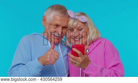 Happy Excited Joyful Senior Couple Man Woman Grandparents Use Mobile Cell Phone Typing Browsing Say