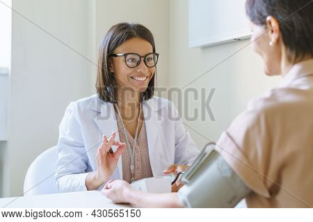 Positive Young African Woman Physician Showing Okay Sign While Checking Patient Blood Pressure With