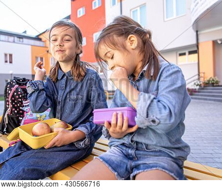 Back To School. Cute Little School Girls Sitting On Bench In School Yard And Eating Lunch Outdoor.