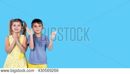 Two Kids Boy And Girl Standing Next To Each Other Smiling Clapping Their Hands And Looking At The Ca