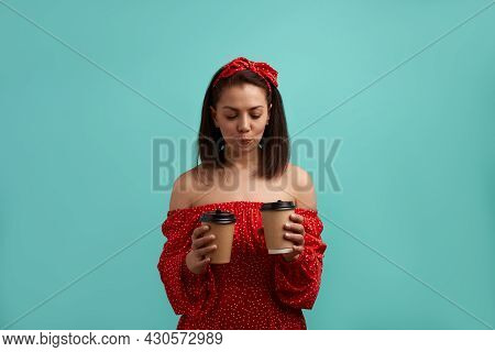 European Woman, Brunette In Red Dress With Bare Shoulders Wearing Hair Band Holds Two Paper Takeaway