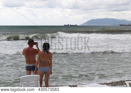 A Guy And A Girl Stand And Watch The Raging Sea. The Guy Takes Pictures Of The Waves On The Phone.