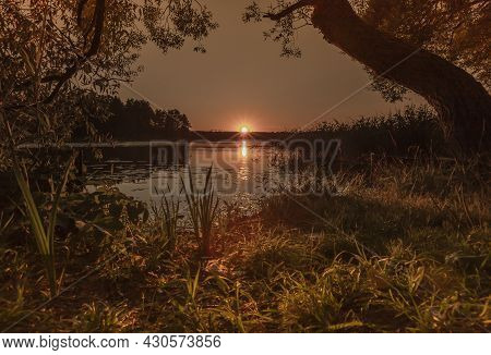 Sunset Over Water With Reflection And Sunbeams In Nature In Summer With Trees And Grass. Calm Peacef