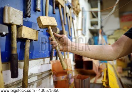 Metalwork Craftsman Working With Metal And Wood At Workshop. Man Using Wooden Hammer. Do It Yourself