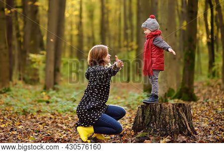 Little Boy With His Young Mother During Stroll In The Forest. Active Family Time On Nature. Fun With