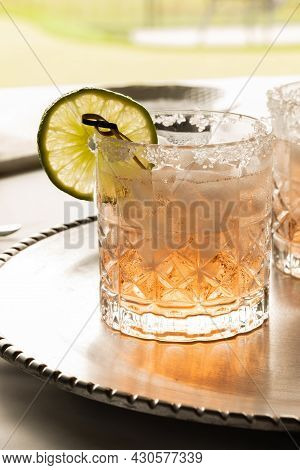 Close Up Of A Margarita Mocktail Garnished With A Slice Of Lime And A Salted Rim, Against A Bright S