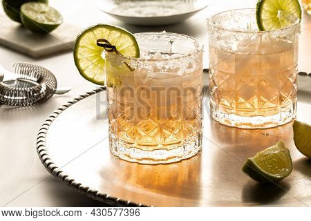 Margarita Cocktails With Salted Rims On A Metal Tray With Ingredients And Strainer In Behind.