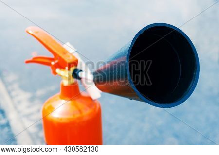 Red Fire Extinguisher With Plastic Nozzle For Emergency Fire Extinguishing. Close-up