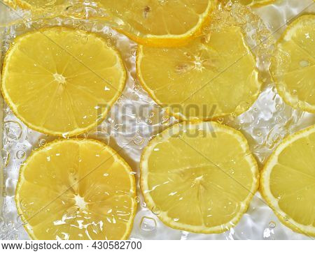 Close-up Fresh Slices Of Yellow Lemon On White Background. Slices Of Lemon In Sparkling Water On Whi