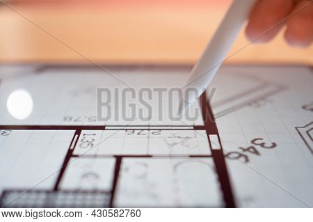 Interior Designer Is Working On A Floor Plan Of A Building On A Mobile