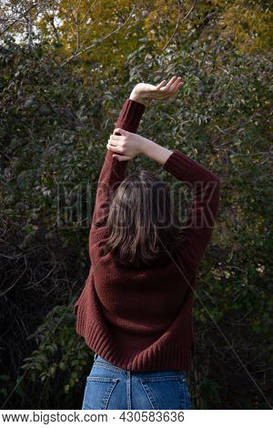 Happy Young Brunette Girl In A Brown Sweater Standing With Raising Her Hands Up In A Forest Scenery.