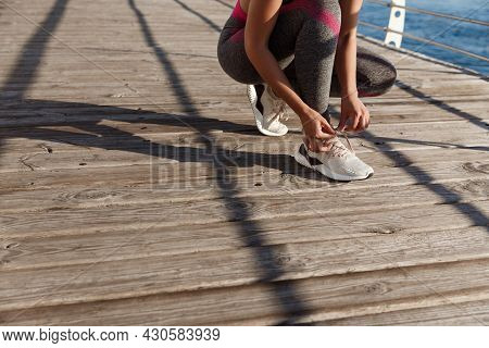 Cropped Shot Of Fitness Woman Tying Her Shoelaces, Prepare For Jogging On The Seaside Promenade