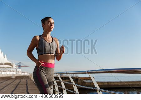 Outdoor Shot Of Young Determined Fitness Woman Jogging Near The Sea, Running Towards Sun Along Seasi