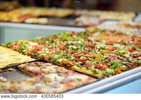 Square Pieces Of Pizza Displayed On The Counter Of Small Italian Pizzeria In Bergamo City, Italy.