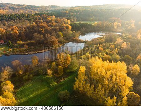 Birds Eye View Of Autumn Forest And A Small Lake. Aerial Colorful Forest Scene In Autumn With Orange