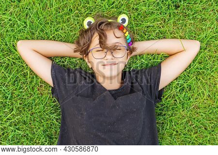 Teenage Girl In Glasses With A Green Rim On Their Hair In The Form Of A Frog And Multi-colored Hair