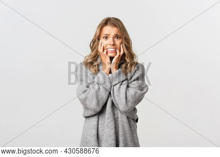 Image Of Scared Blond Woman Trembling From Fear, Looking Frightened And Horrified, Standing Over Whi