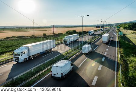 Convoy Or Caravans Of Transportation Trucks Passing Vans And Truck On A Highway On A Bright Blue Day