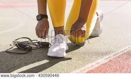 Black Woman In Yellow Sportswear Tying Shoelace On Stadium