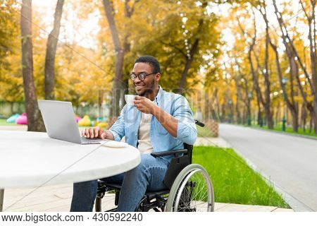 Remote Job For Impaired People. Cheerful Black Guy In Wheelchair Working Online, Using Laptop At Out