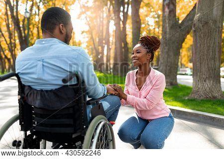 Affectionate Black Woman Holding Her Paraplegic Husbands Hand, Expressing Love At Autumn Park