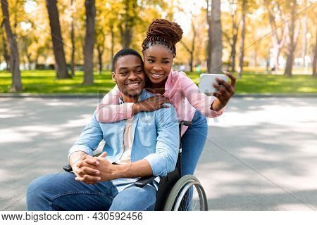Affectionate Black Woman And Her Impaired Boyfriend In Wheelchair Taking Selfie Together At Autumn P