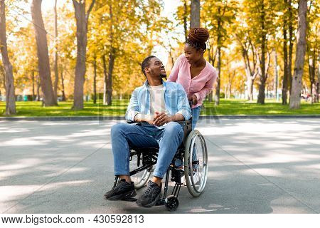 Affectionate Black Woman And Her Disabled Boyfriend In Wheelchair Looking At Each Other On Walk At P