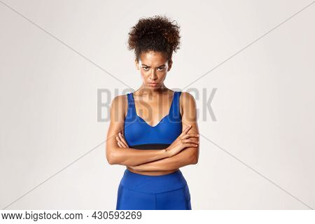 Concept Of Sport And Workout. Angry African-american Fitness Woman, Looking From Under Forehead And