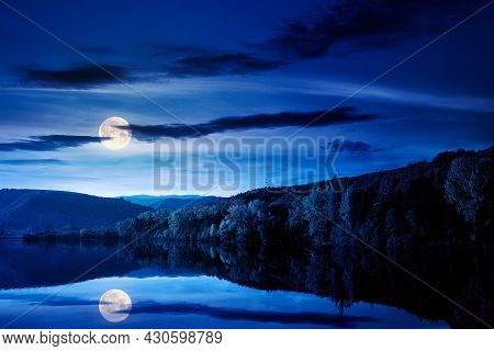 Beautiful Autumn Landscape By The Lake At Night. Forested Mountains Reflecting In The Water Surface
