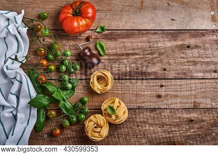 Pasta Tagliatelle, Spices, Basil And Fresh Tomatoes On Old Wooden Rustic Background Table. Food Cook