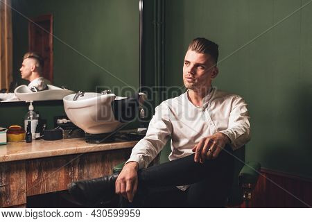 A Young Man With A Beautiful Hairstyle Sits In A Chair In A Barbershop.
