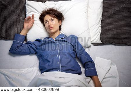 Unhappy Dark Haired Woman In Pajamas Lying In Bed With Opened Eyes While Unable To Sleep At Night. C