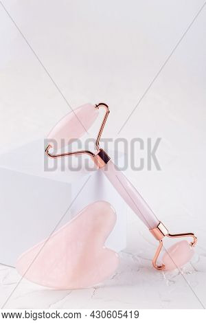 Rose Quartz Crystal Facial Roller And Massage Tool Gua Sha On White Background, Vertical, Copy Space