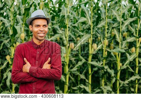 Portrait Of African America Farmer Happy With Arms Crossed With Hat On His Head And Dressed In Red S